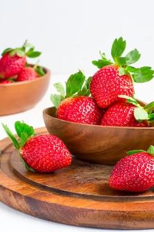Reife erdbeeren in einer großen hölzernen schüssel, selektiver fokus