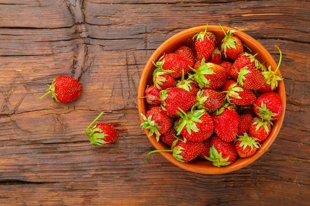 Reife erdbeeren in einer tonplatte auf einem holztisch in der nähe von beeren.