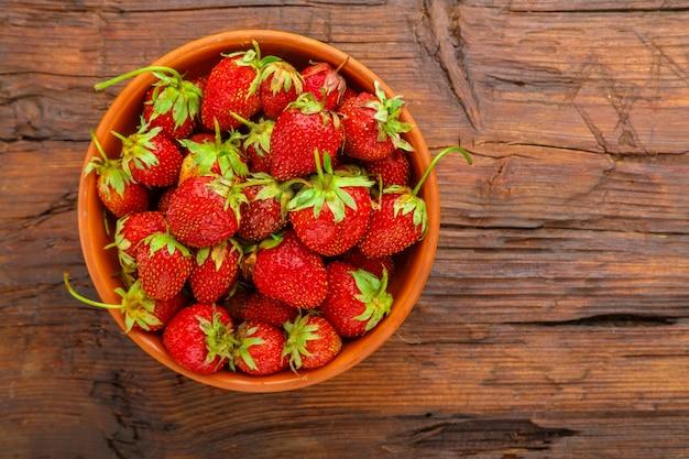 Reife erdbeeren in einer tonplatte auf einem holztisch.