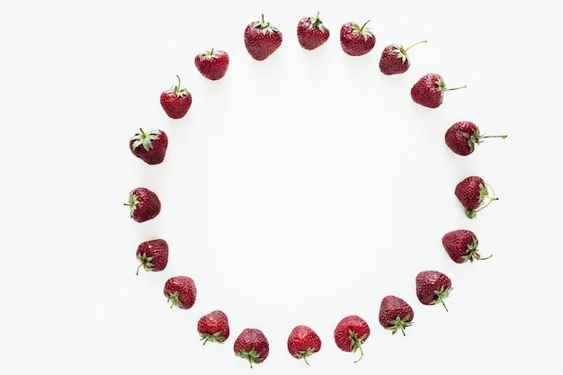 Reife erdbeeren in kreisform auf weißer oberfläche