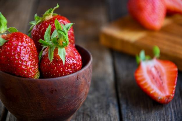 Reife erdbeeren liegen in einer holzschale in der küche auf einem holztisch