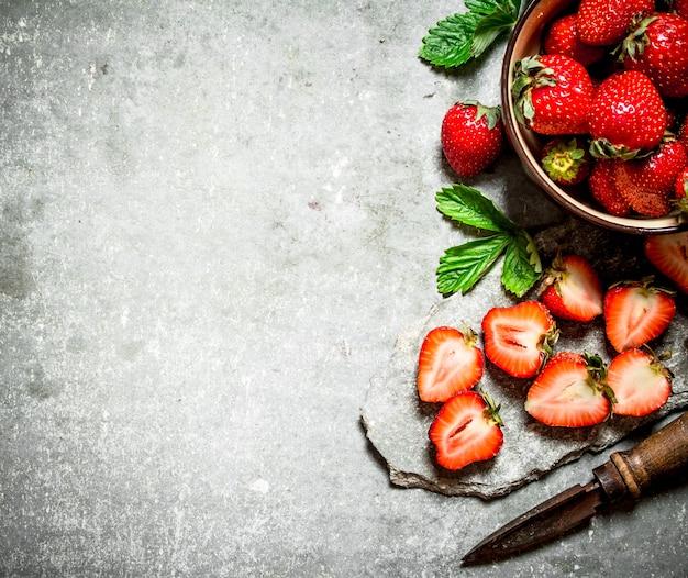 Reife erdbeeren mit einem alten messer auf steintisch.