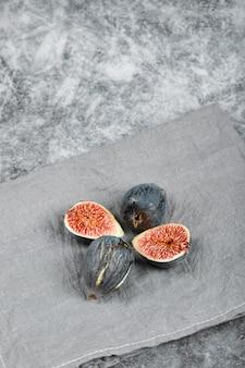 Reife feigen auf marmoroberfläche mit grauer tischdecke