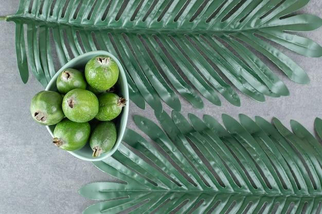 Reife feijoa-früchte in blauer schüssel mit blättern. foto in hoher qualität