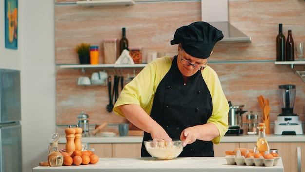 Reife frau bäcker mischen von hand geknackte eier mit mehl in der heimischen küche nach traditionellem rezept. pensionierter älterer koch mit bone, der in glasschüssel gebäckzutaten knetet, die hausgemachten kuchen backen