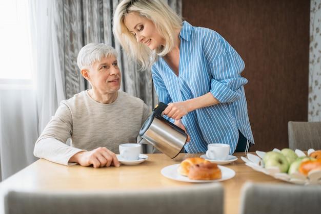 Reife frau behandelt ehemann zum frühstück, glückliche familie zu hause. erwachsenes liebespaar am morgen, frau, die sich um mann kümmert