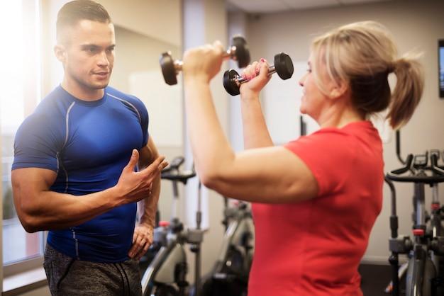 Reife frau beim trainieren mit trainer