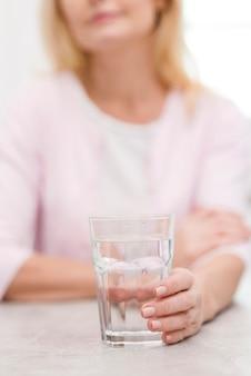 Reife frau der nahaufnahme, die ein glas wasser hält