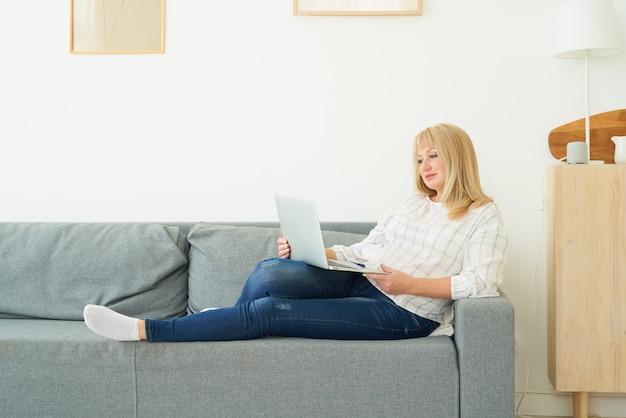 Reife frau der vollen länge unter verwendung des laptops, der auf bequemem sofa, hauptinnenraum liegt