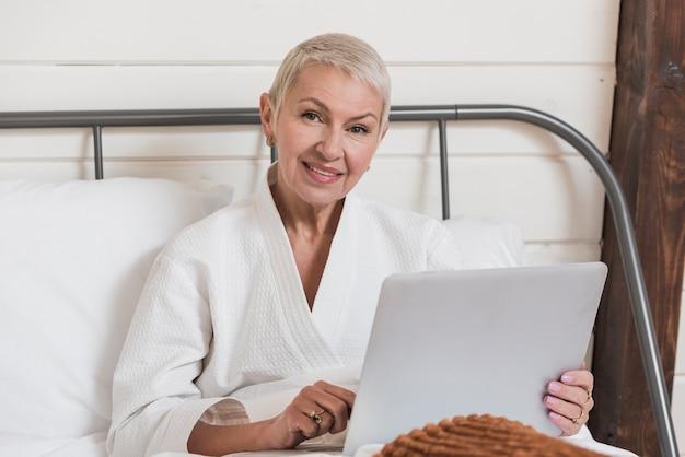 Reife frau der vorderansicht, die auf einem laptop im bett schaut