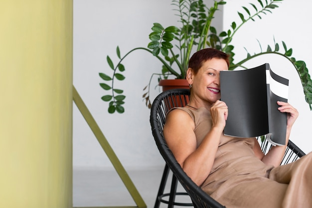 Reife frau der vorderansicht, die auf einem stuhl sitzt
