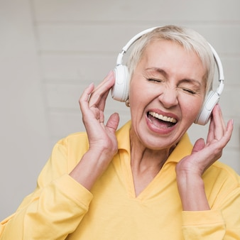 Reife frau der vorderansicht, die musik hört
