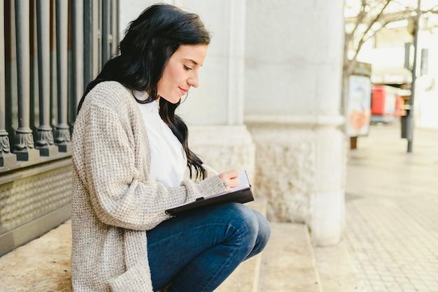 Reife frau des porträts, die kenntnisse in ihrem notizbuch, ihre träume und zukunftspläne zeigend nimmt.