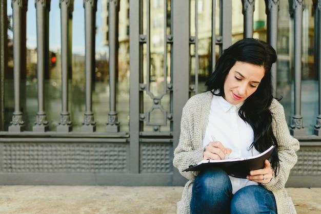 Reife frau des porträts, die kenntnisse in ihrem notizbuch, pläne lesen, vorderansicht nimmt.