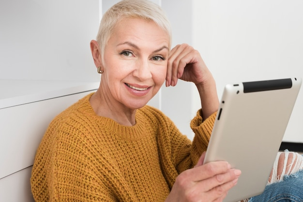Reife frau des smiley, die tablette hält