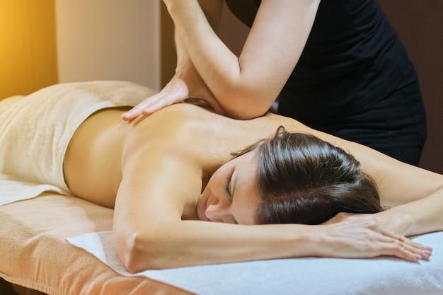 Reife frau, die auf massagetisch liegt und medizinische rückenmassage, pflege und behandlung von menschen mittleren alters erhält