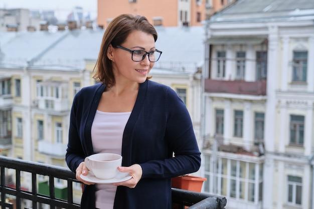 Reife frau, die auf offenem balkon mit tasse tee steht