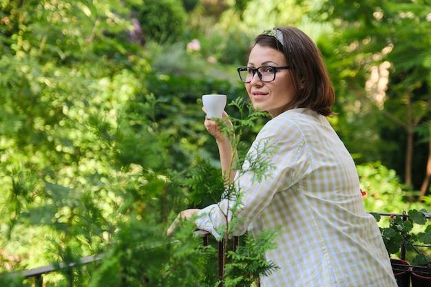 Reife frau, die auf offenem balkon steht, weibliche frau mit tasse kaffee allein