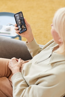 Reife frau, die auf sofa sitzt und handy vor ihrem gesicht hält, hat sie online-gespräch mit freunden