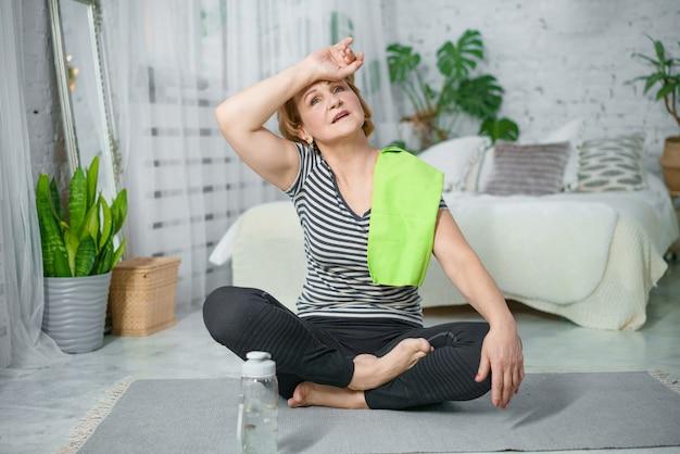 Reife frau, die auf übungsmatte nach fitness-training ruht