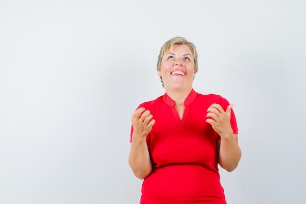 Reife frau, die aufschaut, hände im roten t-shirt hebt und glücklich schaut.