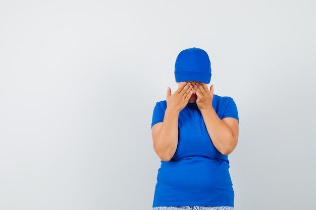 Reife frau, die augen mit händen im blauen t-shirt bedeckt und amüsiert schaut.