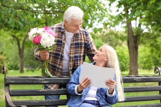 Reife frau, die blumen von ihrem ehemann im park empfängt