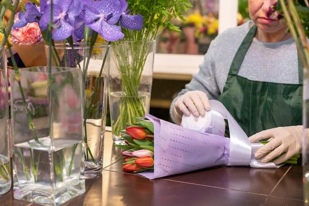 Reife frau, die blumenstrauß mit tulpen einwickelt