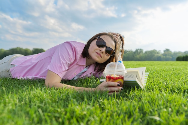 Reife frau, die buch liest, frau, die auf grünem gras mit getränk liegt