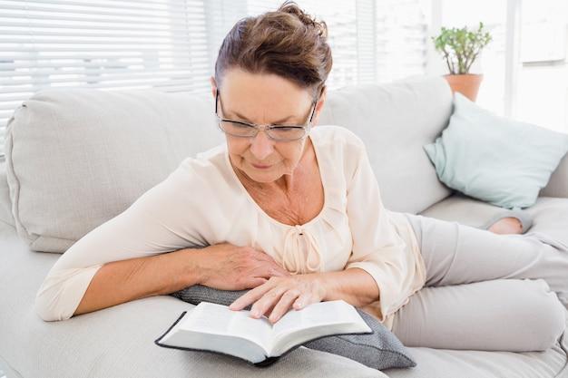 Reife frau, die buch liest, während sie auf sofa ruht