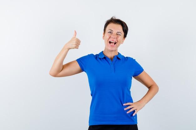 Reife frau, die daumen oben im blauen t-shirt zeigt und selbstbewusst, vorderansicht schaut.
