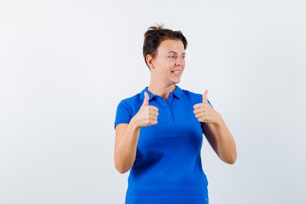 Reife frau, die doppelte daumen oben im blauen t-shirt zeigt und glücklich schaut. vorderansicht.