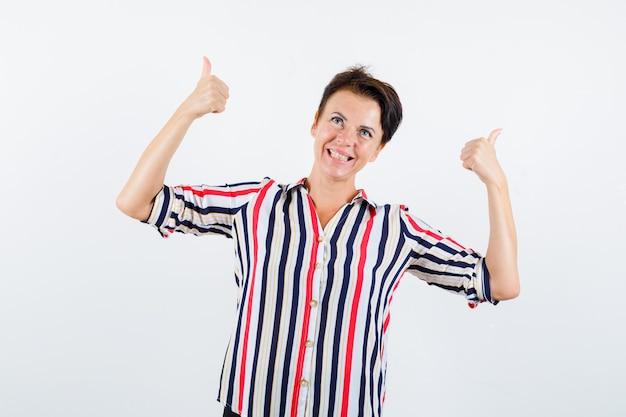 Reife frau, die doppelte daumen oben im gestreiften hemd zeigt und glücklich schaut. vorderansicht.