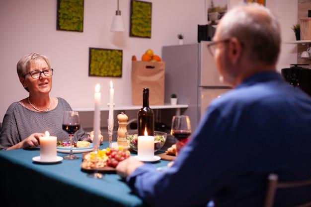 Reife frau, die ein gespräch mit ehemann hat, während sie ein glas rotwein in der küche hält. älteres paar sitzt am tisch in der küche, redet, genießt das essen, feiert ihr jubiläum in