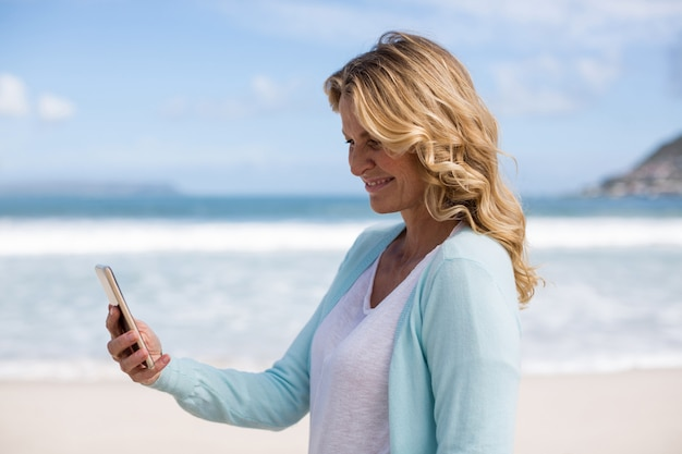 Reife frau, die ein selfie vom handy am strand nimmt