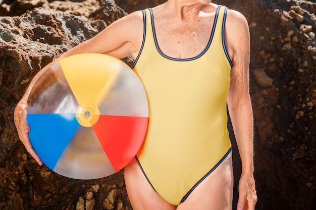 Reife frau, die einen strandball in einem badeanzug hält