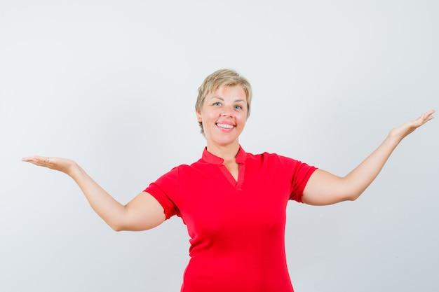 Reife frau, die etwas im roten t-shirt zeigt oder vergleicht und fröhlich aussieht.