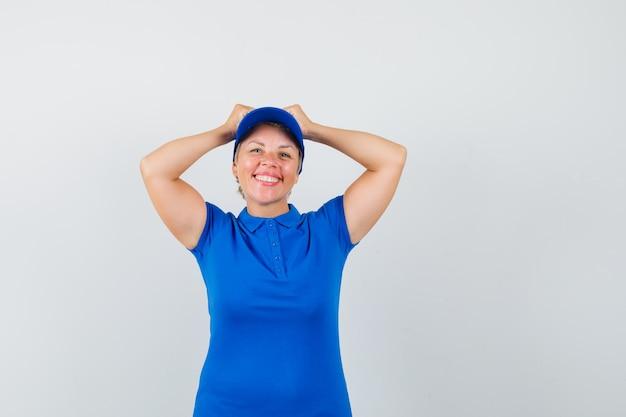 Reife frau, die hände auf kopf im blauen t-shirt hält und fröhlich schaut.