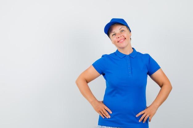Reife frau, die hände auf taille im blauen t-shirt hält und zuversichtlich schaut