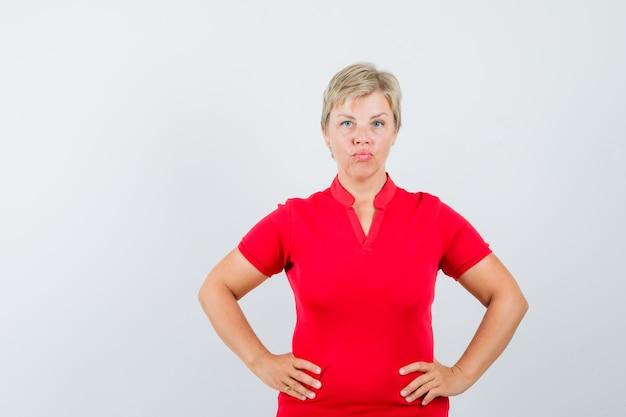 Reife frau, die hände auf taille im roten t-shirt hält und ernst schaut.