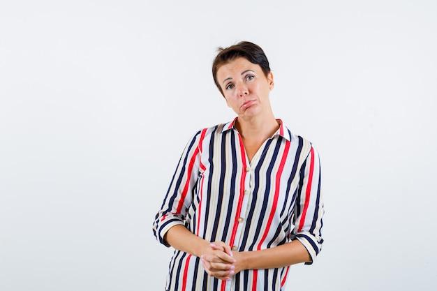 Reife frau, die hände fasst, lippen in gestreifter bluse krümmt und mürrisch schaut, vorderansicht.