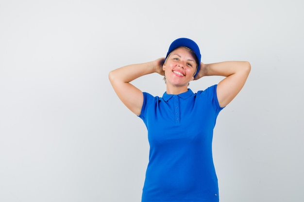 Reife frau, die hände hinter kopf im blauen t-shirt hält und entspannt schaut.
