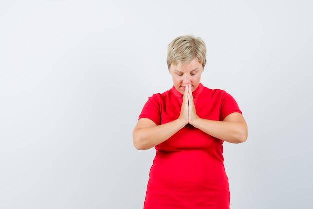 Reife frau, die hände in der gebetsgeste im roten t-shirt hält und hoffnungsvoll aussieht