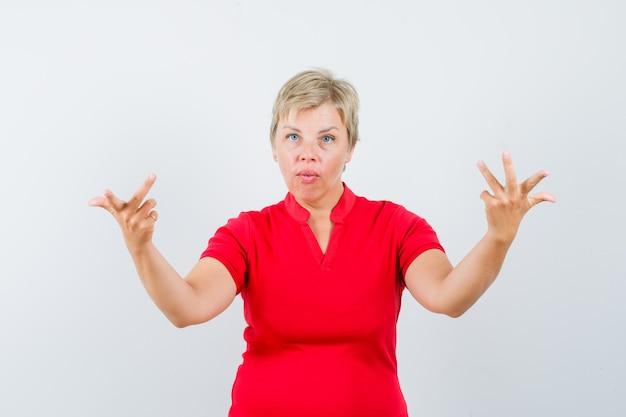 Reife frau, die hände in verwirrter geste im roten t-shirt erhebt.