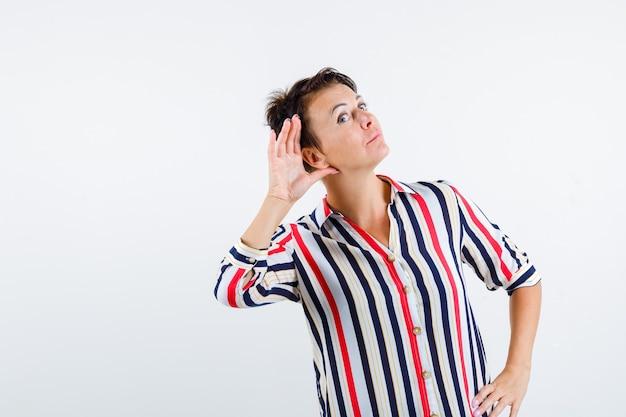 Reife frau, die hand auf taille hält, hand nahe ohr hält, um in gestreifter bluse zu hören und fokussierte vorderansicht zu schauen.