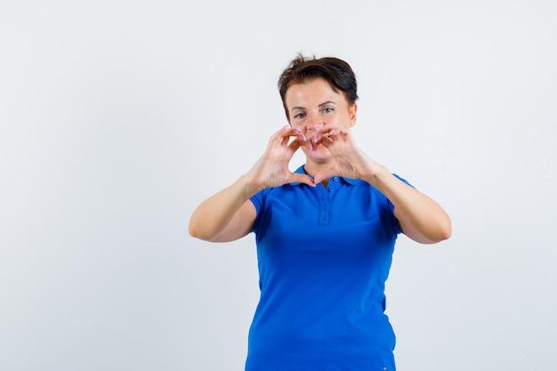 Reife frau, die herzgeste im blauen t-shirt zeigt und fröhlich, vorderansicht schaut.
