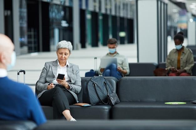 Reife frau, die ihr handy benutzt, während sie am flughafen sitzt und auf ihren flug wartet