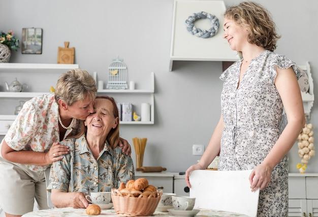 Reife frau, die ihre ältere mutter in der küche küsst