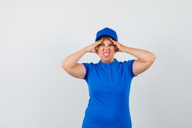 Reife frau, die ihre haut auf stirn in blauem t-shirt zieht