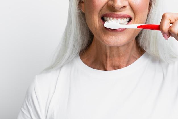 Reife frau, die ihre zähne säubert